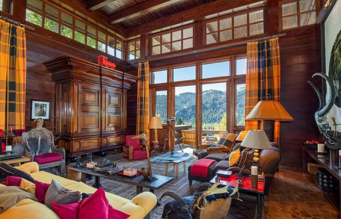 Living room with wood paneling and wall of windows