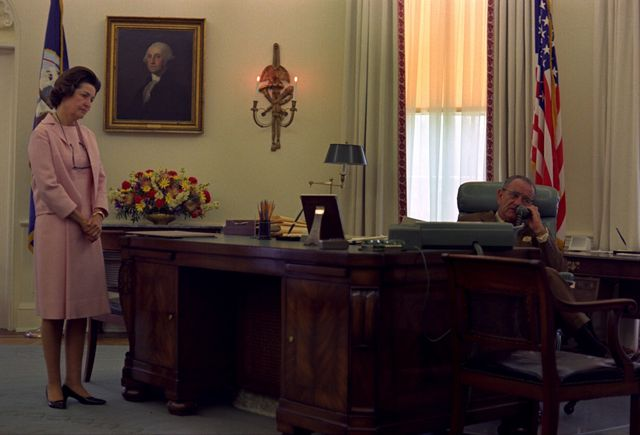 """LBJ sits behind the Johnson desk with his wife, Claudia """"Lady Bird"""" Johnson, by his side."""