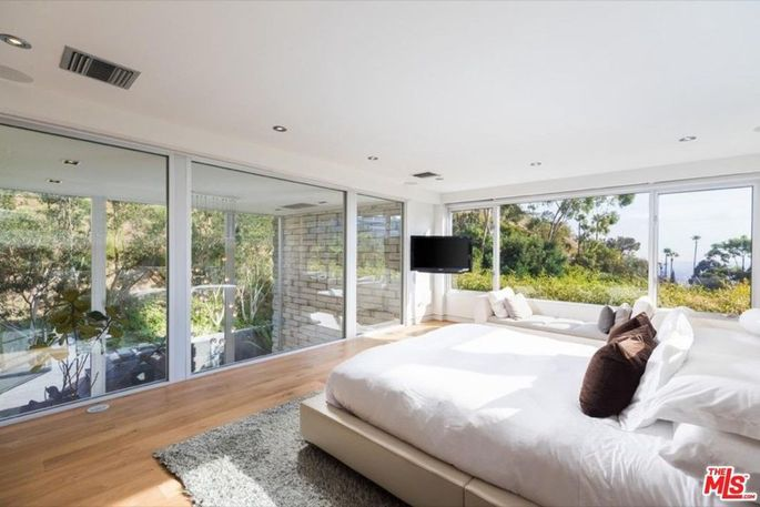 This master bedroom invites the outdoors in thanks to the floor-to-ceiling windows.