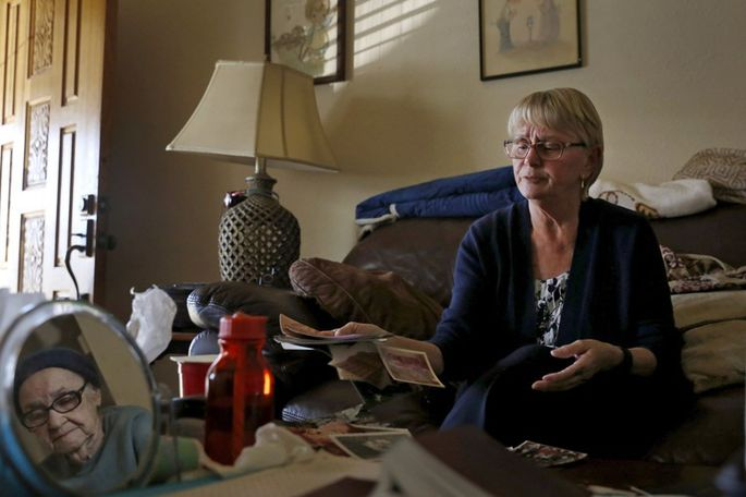 Cindi Ventura helps her mother sort old family photographs. She says she was confused about terms of their PACE loan because it was called an assessment.