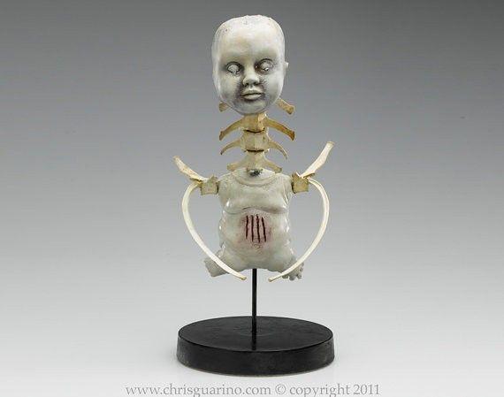 baby doll and vertebrae sculpture