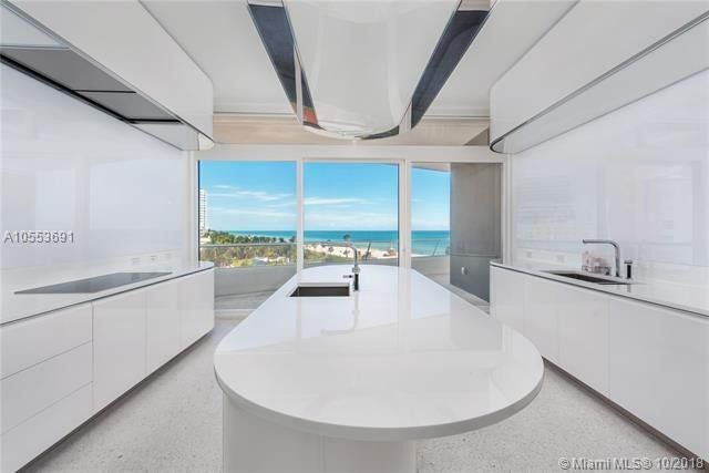 Sleek white kitchen includes an adjoining breakfast nook.