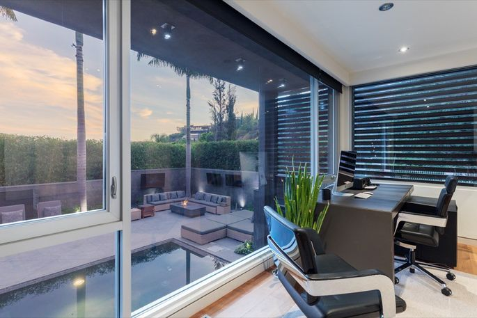 Combining business with pleasure, the home office overlooks the pool.