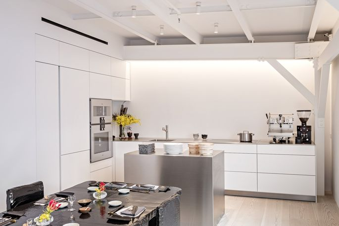 Stephanie Goto's kitchen has white laminated Bulthaup cabinets and Gaggenau appliances. The layout optimizes efficiency and easy access to tools and appliances. The island conceals stacked drawers.