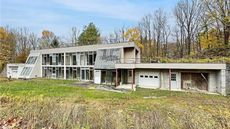 Built Into a Hillside, This Concrete and Glass Fixer-Upper Is on Sale for Only $99,900