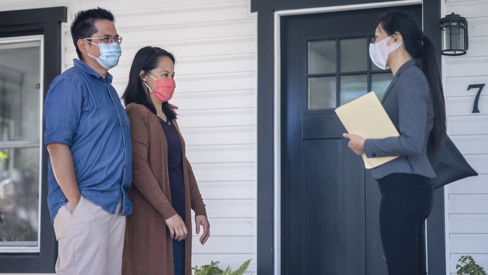 Real Estate agent meeting with clients in masks