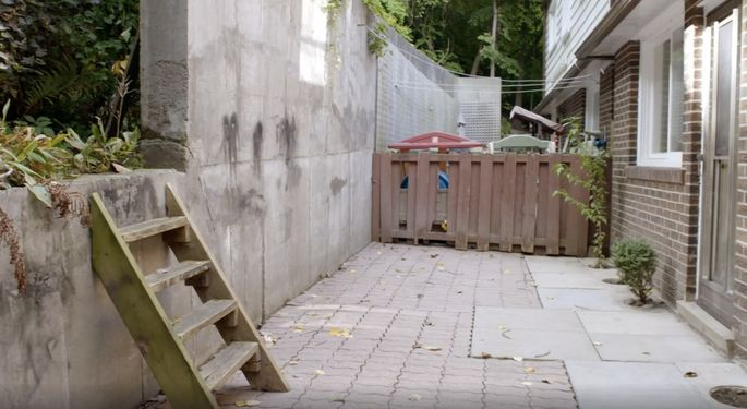 This house is surrounded by trees, but the view in the backyard is mostly concrete.