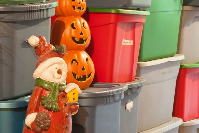 Plastic storage bins filled with decorations for various holidays