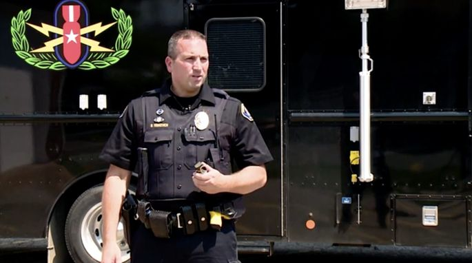 """Patrol officerBrian Yenkevich with a """"pineapple"""" hand grenade."""