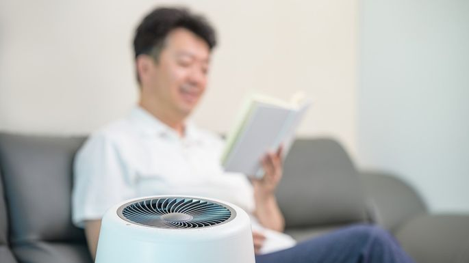 An Asian middle-aged man reading in the living room with an air purifier on. Blur background.
