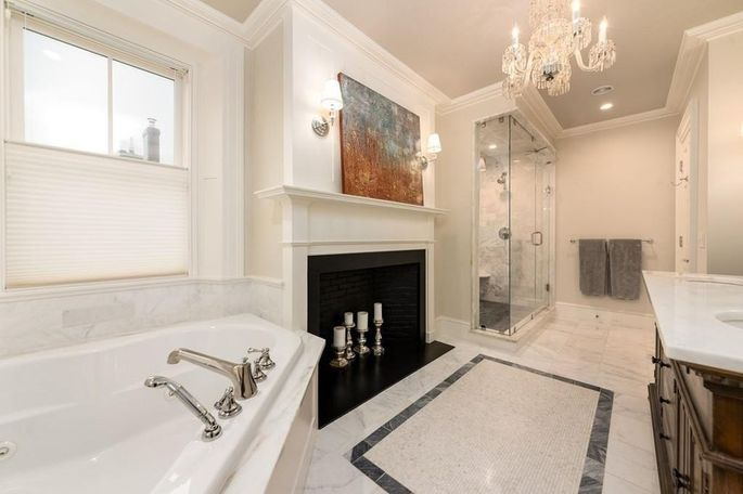 Keeping the chandelier well above and far from the tub is your best bet.