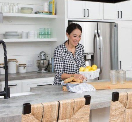 This kitchen designed by Joanna Gaines features two of her signature touches: shiplap and open shelving with country accessories.