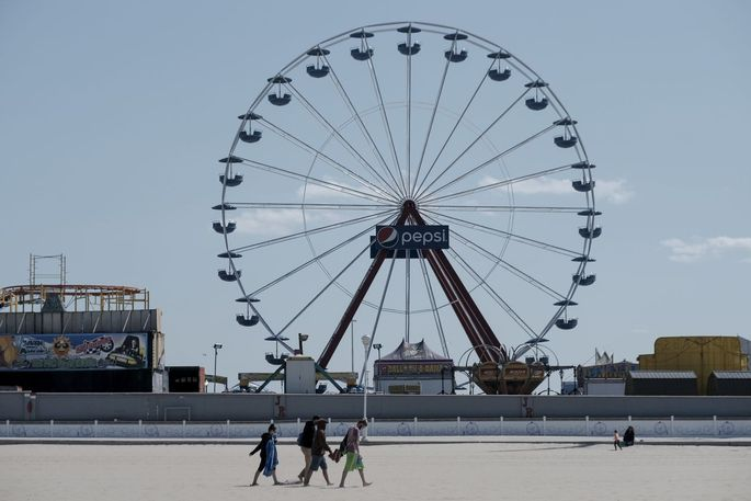 Beachgoers walk toward the boardwalk at Ocean City, Md., on May 13.