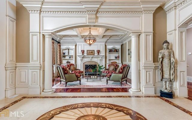 Foyer with marble flooring and white columns