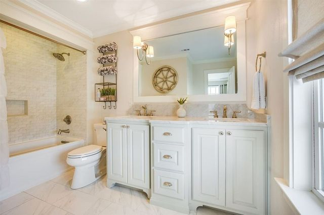 Gleaming white master bath with brass fixtures.