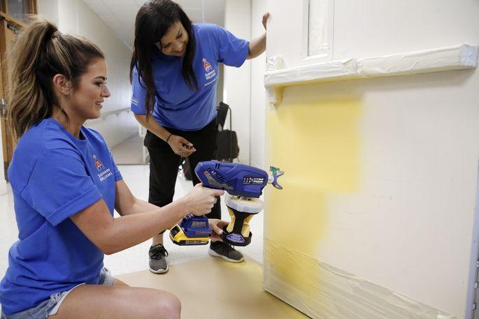 Carla Zenn, right, looks on as JoJo Fletcher paints a gym door.