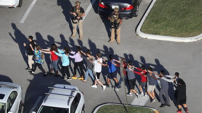 People are brought out of the Marjory Stoneman Douglas High School after the shooting at the school.