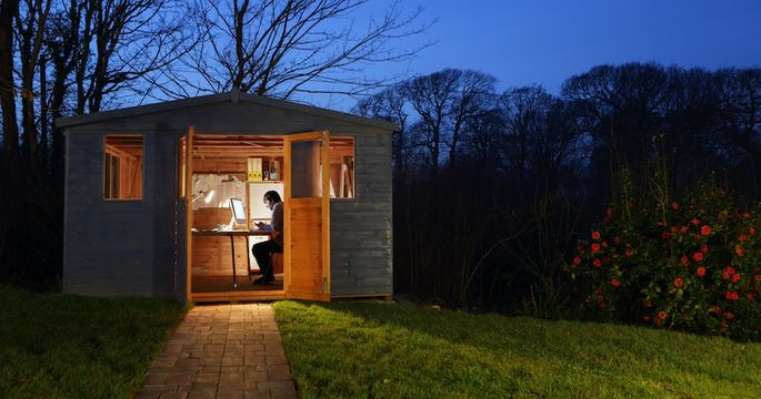 Man working in garden shed at night