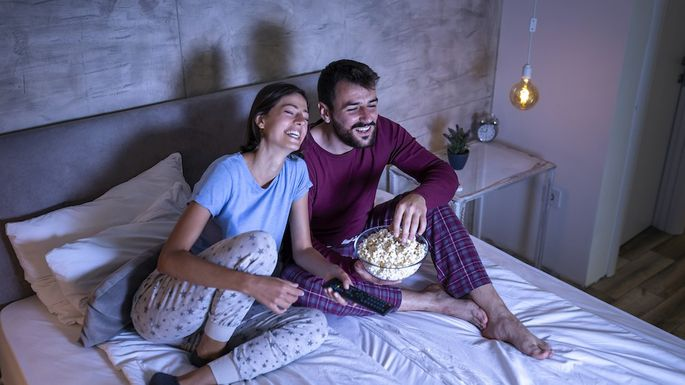 Couple watching a movie in bed