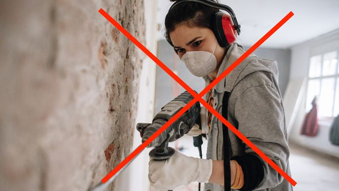 Woman using drilling machine during reconstruction of her apartment