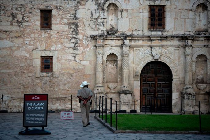 A police officer walks outside of the closed Alamo in San Antonio, TX.