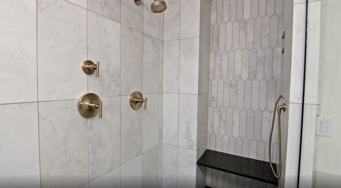 The tiles in this shower mix different shapes to create dimension.
