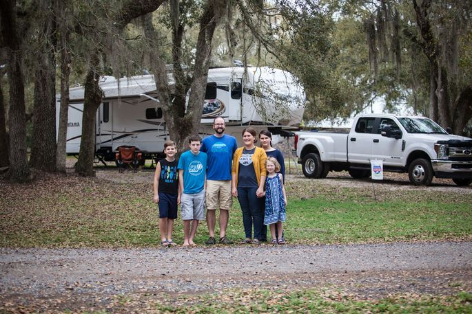 The Denkins family in front of their recreational vehicle.\