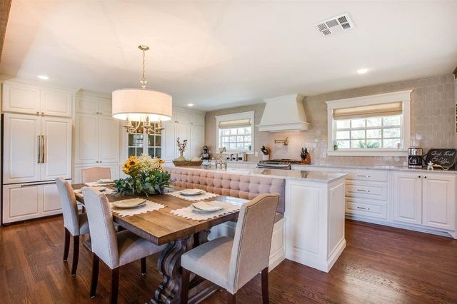 Joanna Gaines designed kitchen island with dining table and booth seating attached.