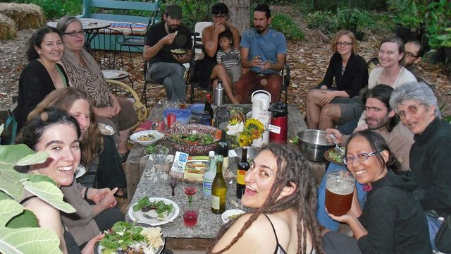 Members of the Los Angeles Eco-Village having a potluck meal with neighbors.