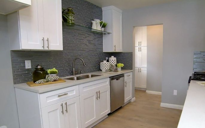 The white counters and the ceiling-high backsplash make this kitchen look bigger.