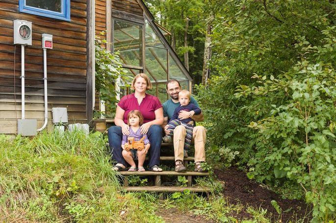 The Adamants with their 3-year-old daughter and 1-year-old son on the steps to the greenhouse.