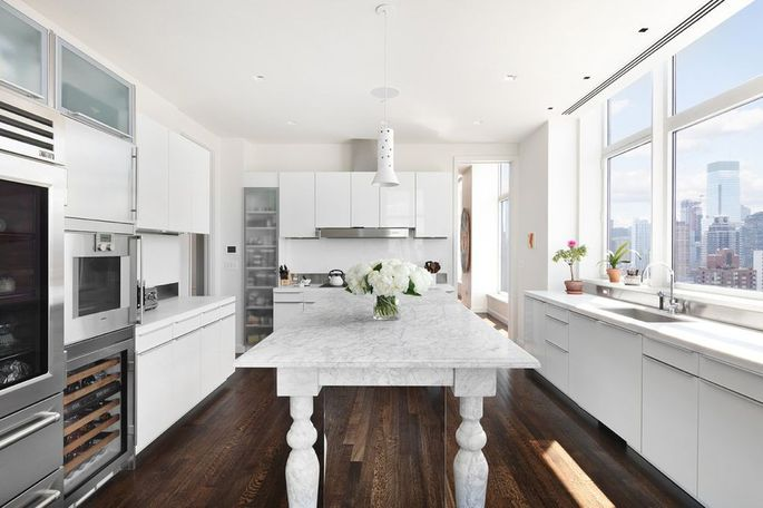 The kitchen features Carrara marble countertops, Sub-Zero wine cooler and refrigerator, and a Gaggenau dishwasher.