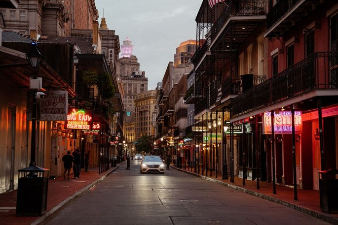 A car drives down Bourbon Street in New Orleans on a Saturday, when it would normally be crowded with revelers.