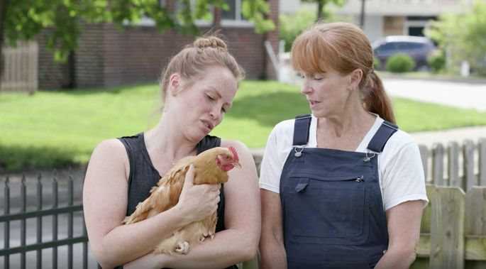 Karen Laine and Mina Starsiak hang out in Laine's yard with one of her chickens.
