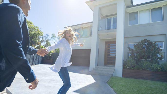 Couple joyfully running into their new home.