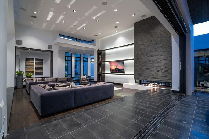 Living room with fireplace and retractable glass walls