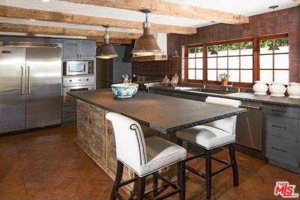 The island in the kitchen is made of rustic wood cabinetry with a soapstone counter.