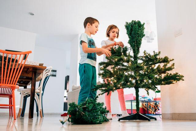 Kids putting up an artificial Christmas tree