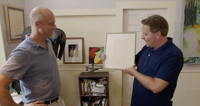 Paxton holds the Picasso sketch that was found in the house.