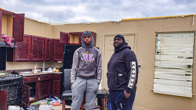 Jamontae Ceasar and his father, Kelvin Worthy, stand in the kitchen of their home after the roof was blown off in a tornado.