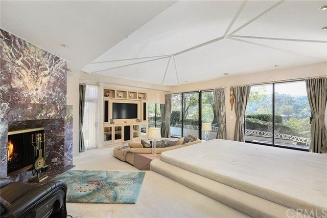 Master suite with marble fireplace and raised platform for the bed