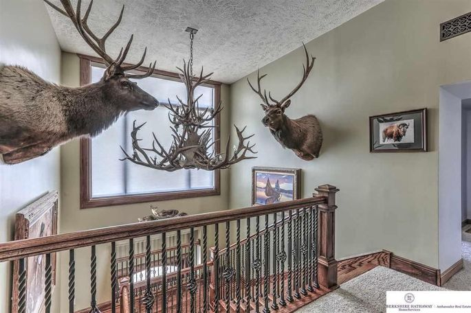 Mounted hunting trophies flank the entryway chandelier.