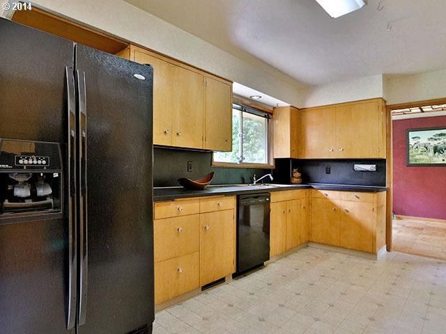Old appliances and cabinetry give the room a dated look.