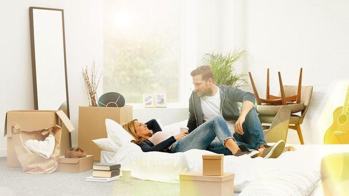 Peaceful young couple lying among unpacked boxes