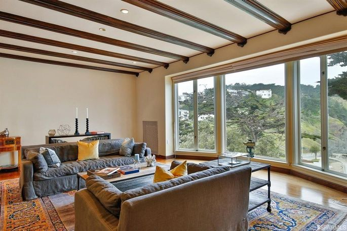 Living room with beamed ceiling and picture windows