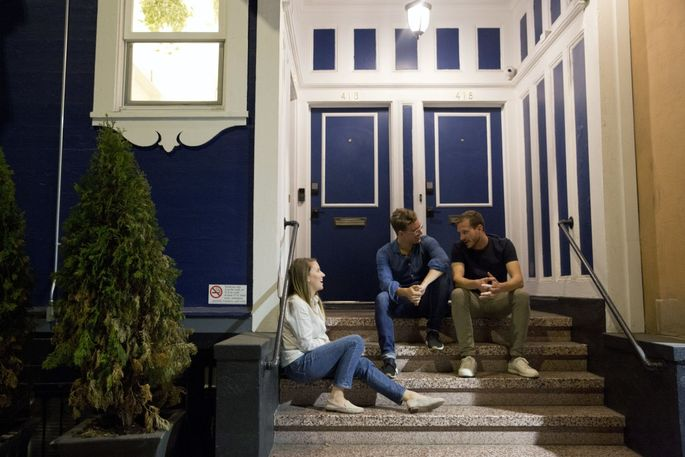 From left, Ellie Logan, Esteve Almirall and Josh Lehman hang out on the front stoop of the Starcity SoMa residence in San Francisco.