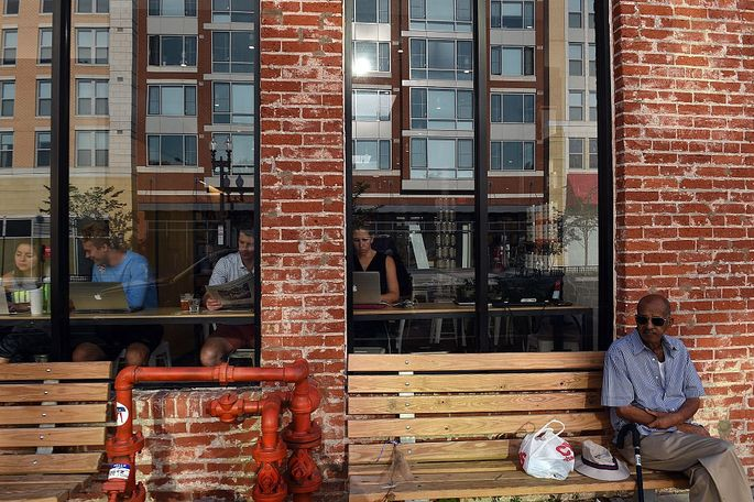 New apartments are reflected in the window glass of a trendy cafe in Washington's Shaw neighborhood.