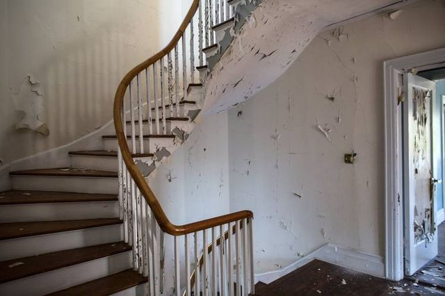 Peeling paint and a stairway inside Soundview Manor that is designated as a historic landmark.