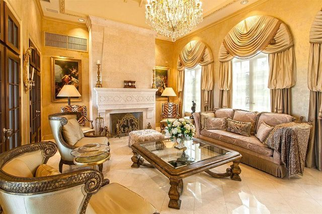 A luxe living room featuring gold curtains, a chandelier, and a pair of tiger-print armchairs.