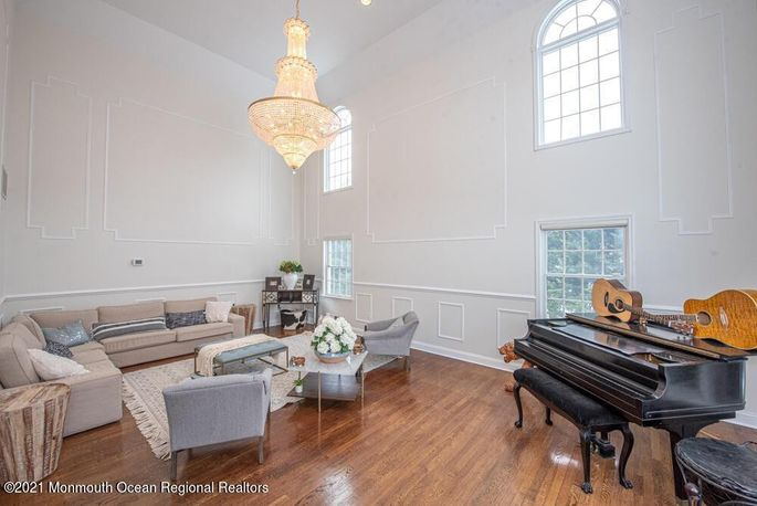Soaring arched windows are in both the living room and foyer.